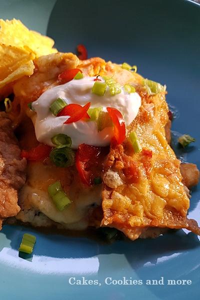 Chilaquiles mit Käse und Poulet, garniert mit Sauerrahm, Chilis und Zwiebeln